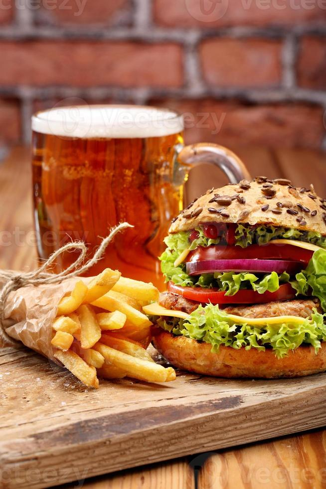 Grilled hamburger with fries and beer on brick wall background photo