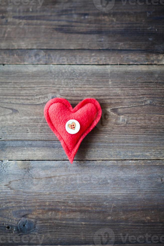 Red fabric heart on wooden background photo