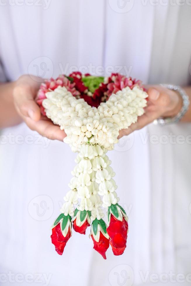 soft light tone with Jasmine garland of flowers on hand photo