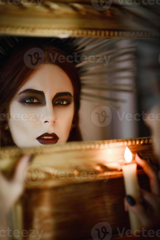 Beautiful witch holding candle in hand and looking into mirror photo