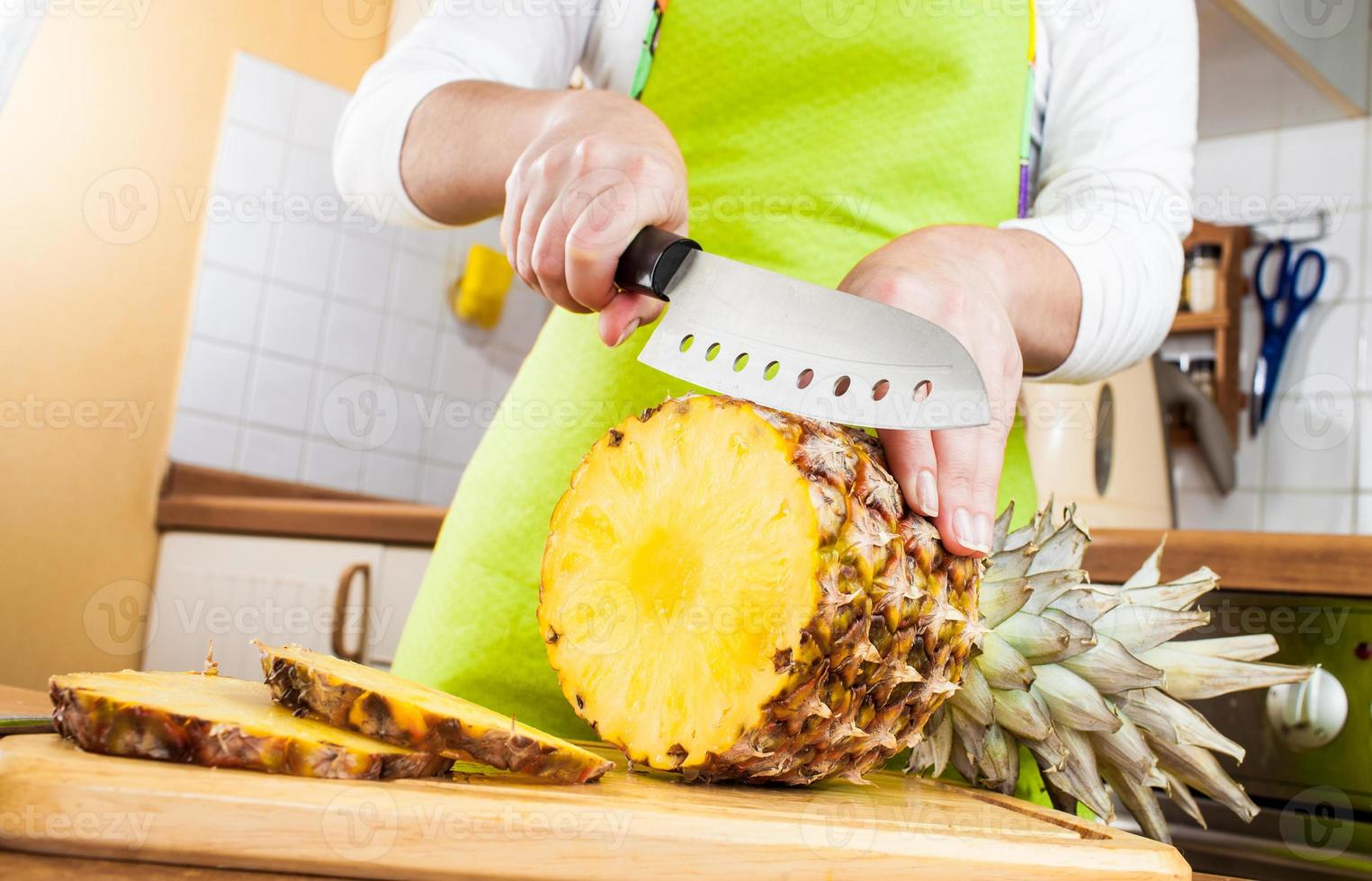 Woman's hands cutting pineapple photo