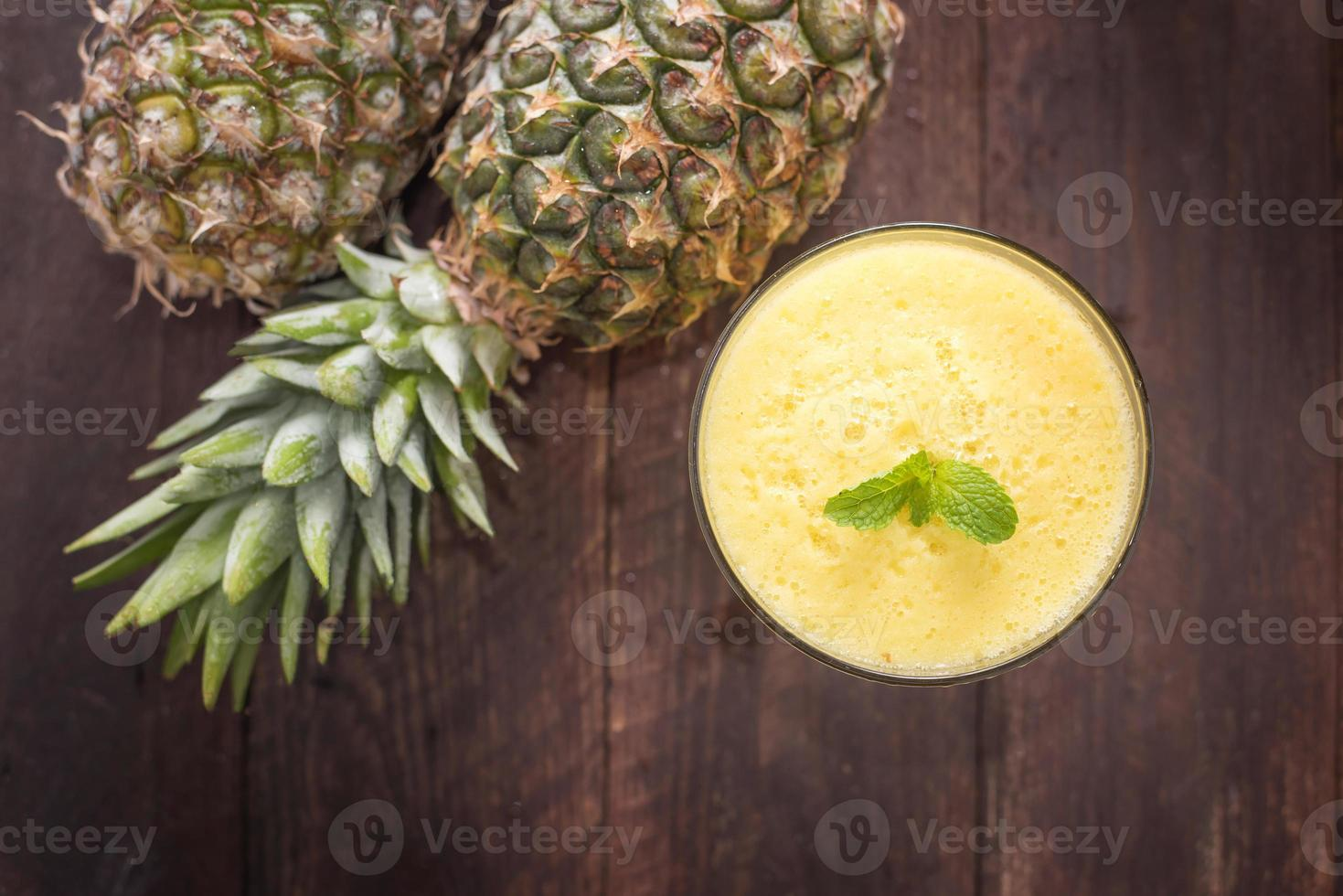 Top pineapple smoothie on wooden table photo