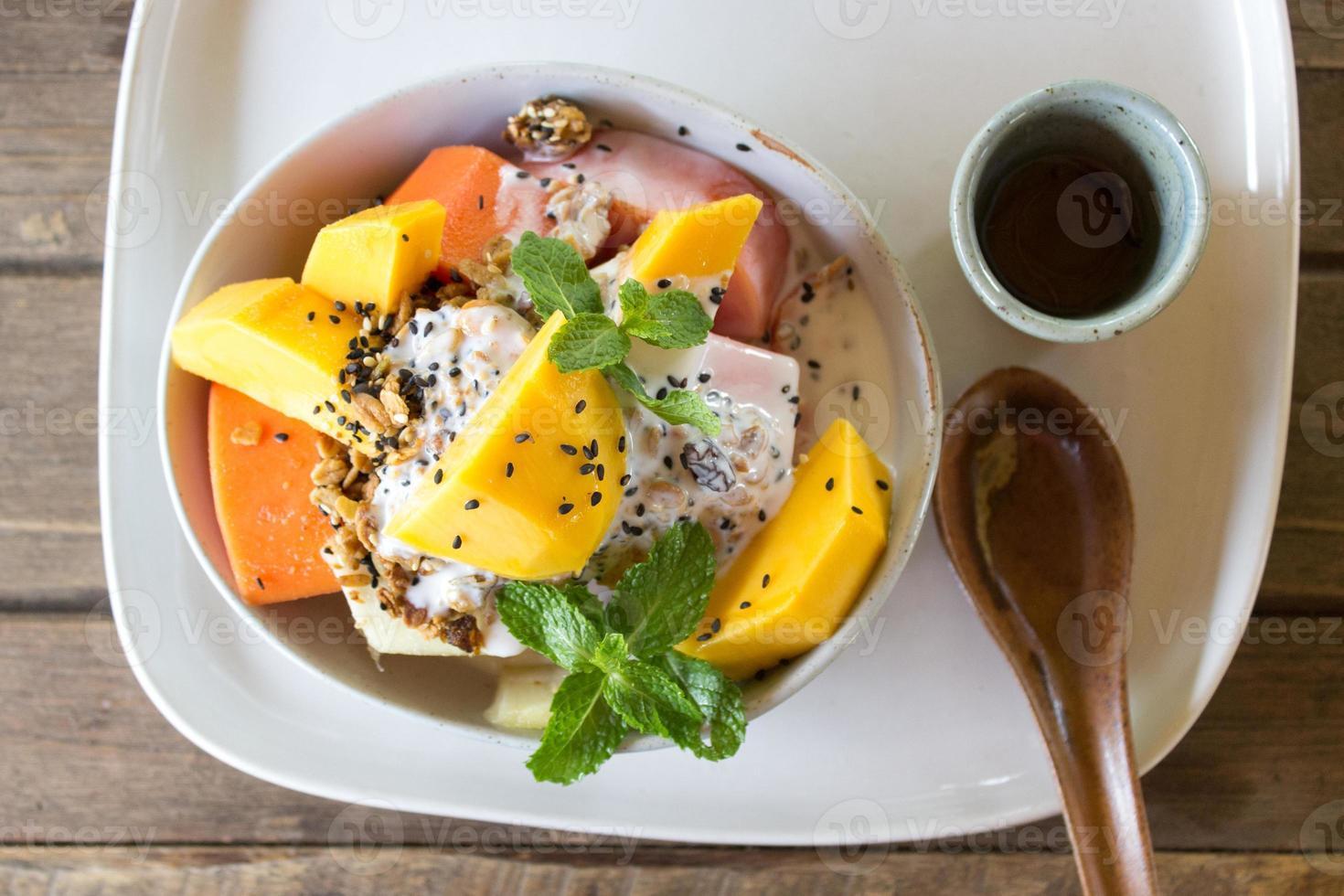 Ensalada de frutas exóticas con muesli y yogurt foto