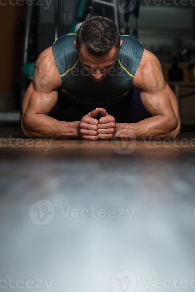 joven haciendo flexiones en el gimnasio foto