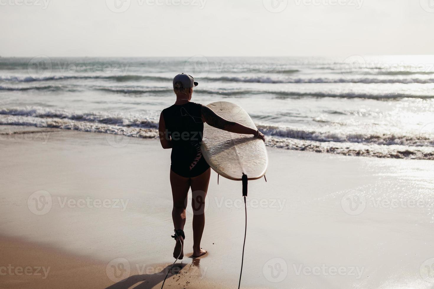 mujer surf con vista trasera de la tabla de surf foto