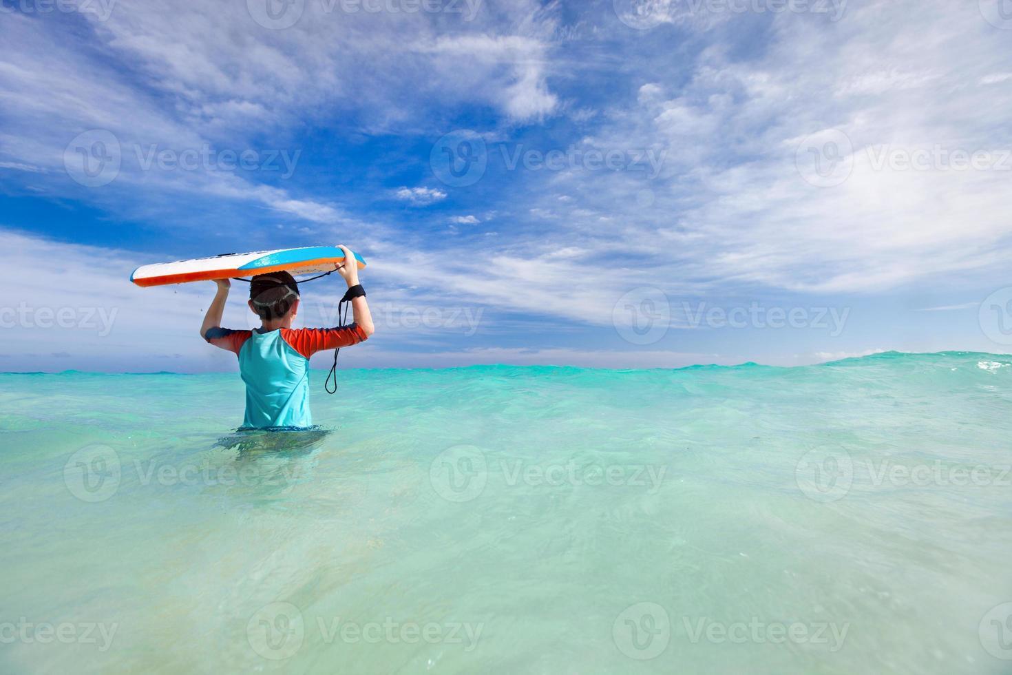 niño con tabla de surf foto