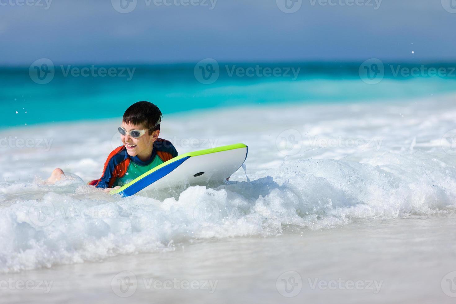 niño nadando en boogie board foto