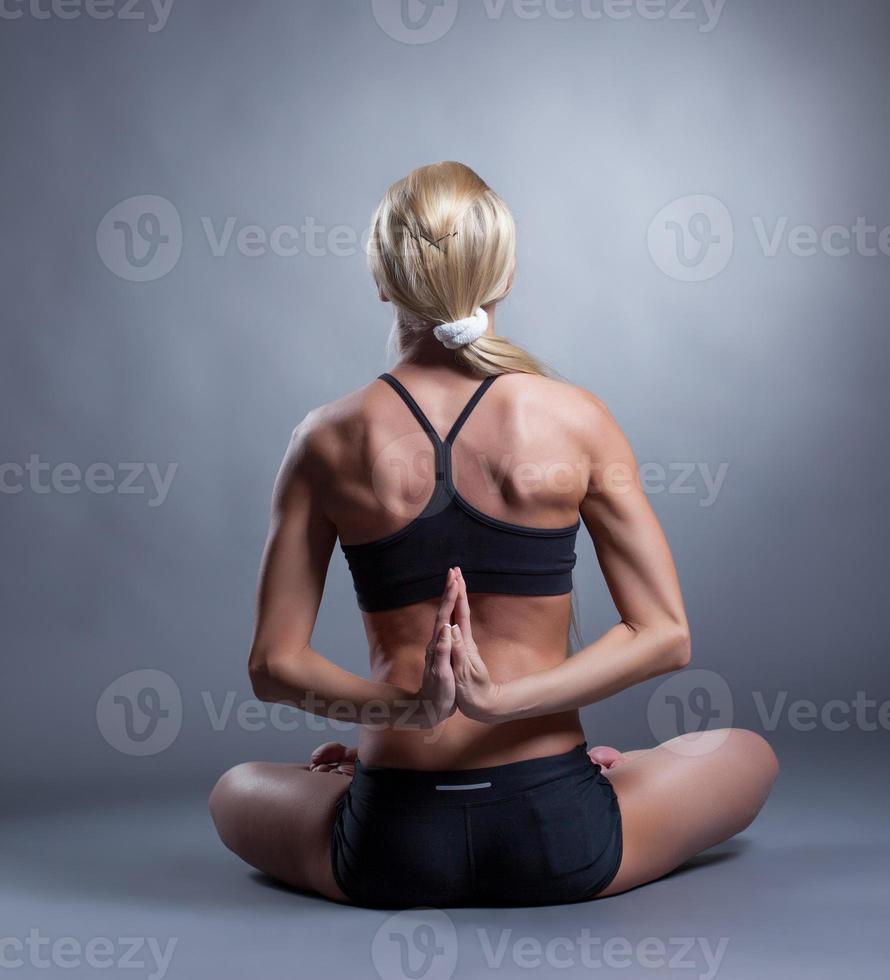 mujer flexible dobla las manos a la espalda foto