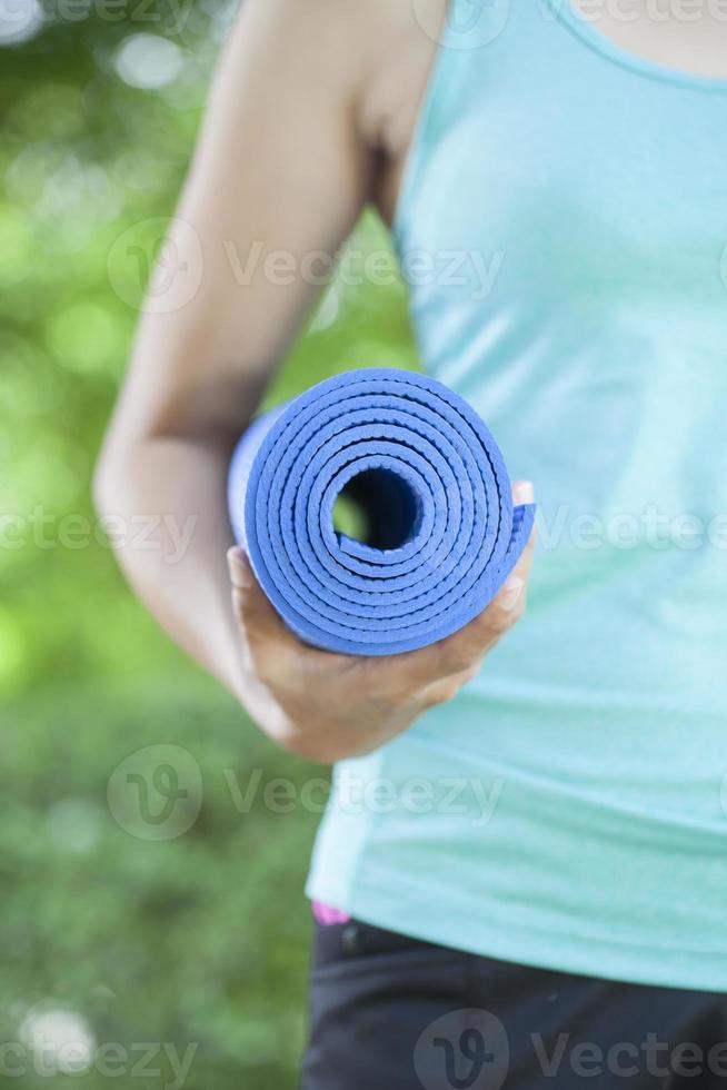 joven mujer sosteniendo una estera de yoga foto