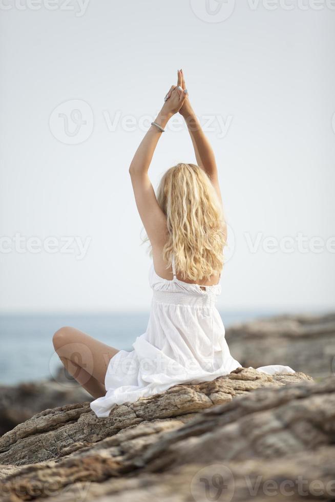 mujer practicando yoga en la playa foto