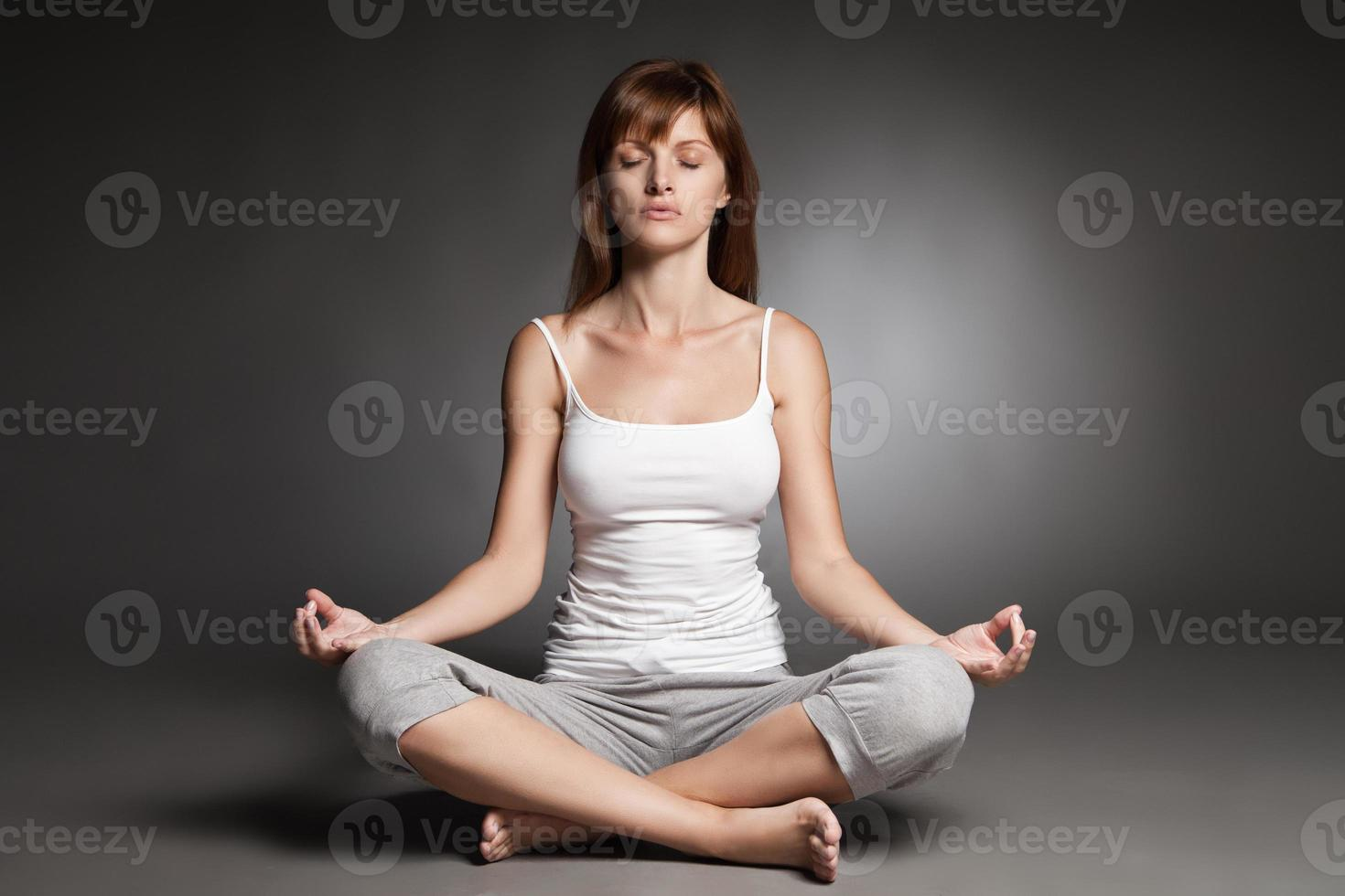 mujer joven haciendo yoga sobre fondo oscuro foto