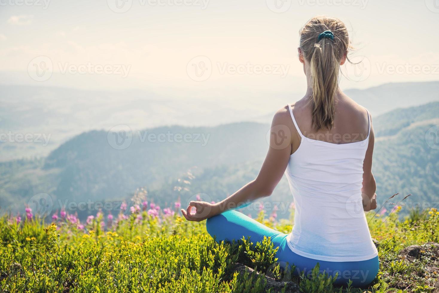 mujer joven medita en la cima de la montaña foto