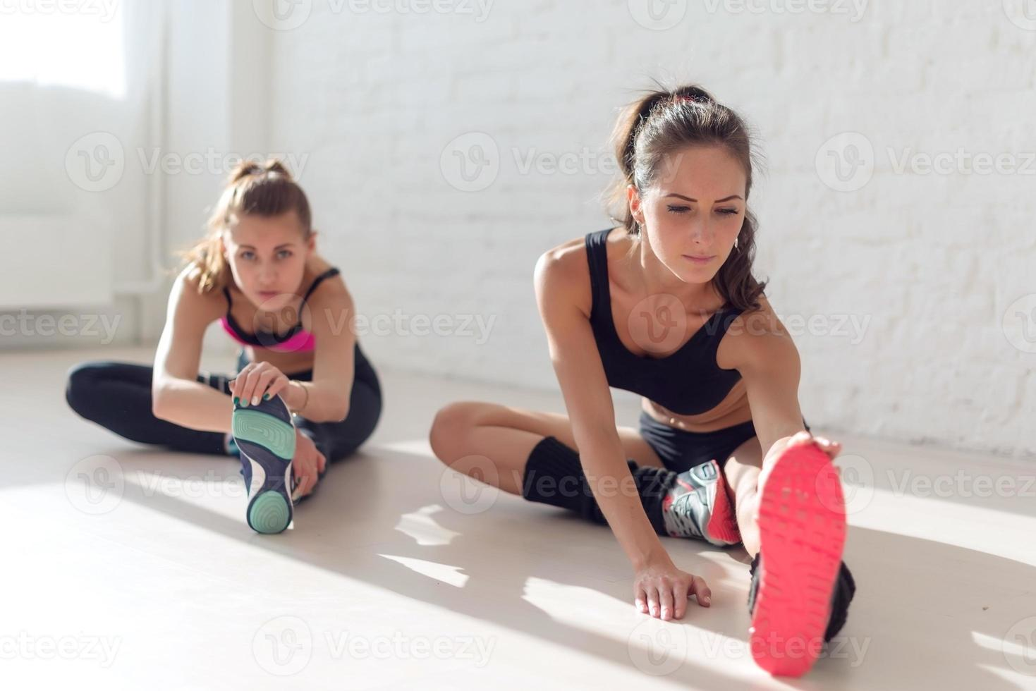 Grupo de mujeres en forma trabajando estirando los músculos de las piernas de nuevo a foto