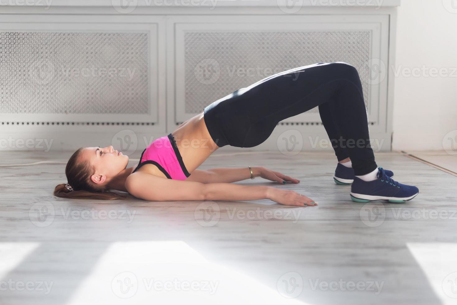 Vista lateral de la joven haciendo gimnasia el medio puente foto