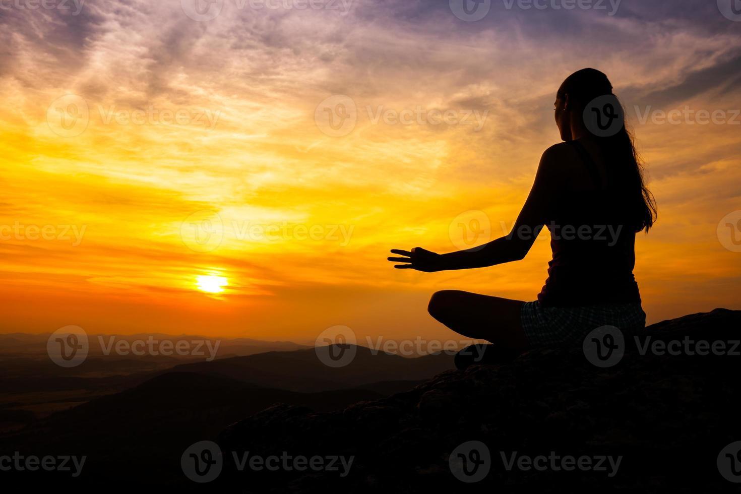 practicante de yoga en puesta de sol foto