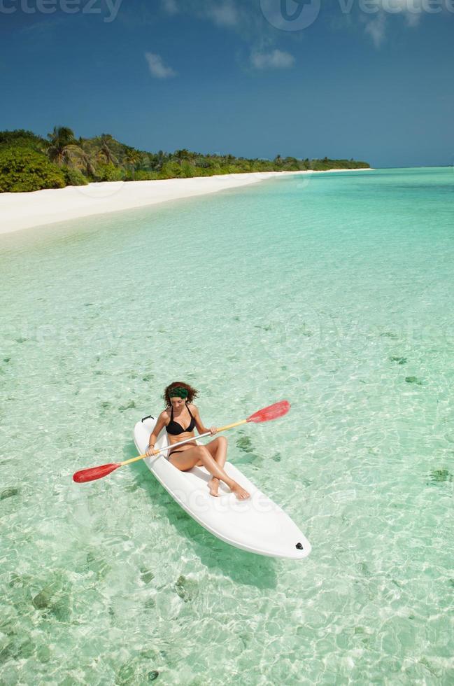 Linda mujer nadando en la canoa foto