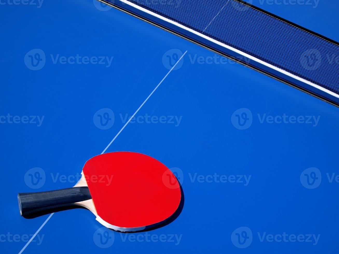 mesa de tenis azul y bate de ping pong rojo foto