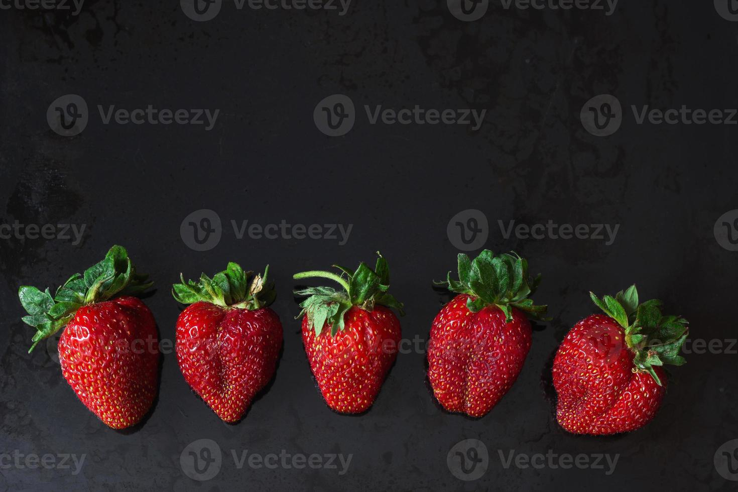 fresas rojas en una fila sobre negro foto