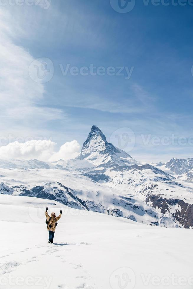 Man standing on the snow in the background of Matterhorn. photo