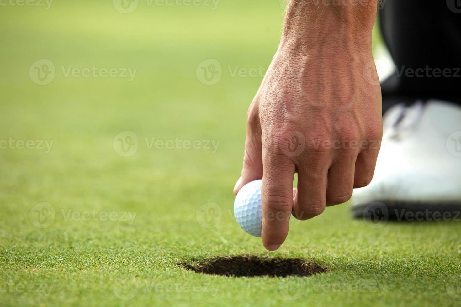 Persona sujetando una pelota de golf, primer plano foto