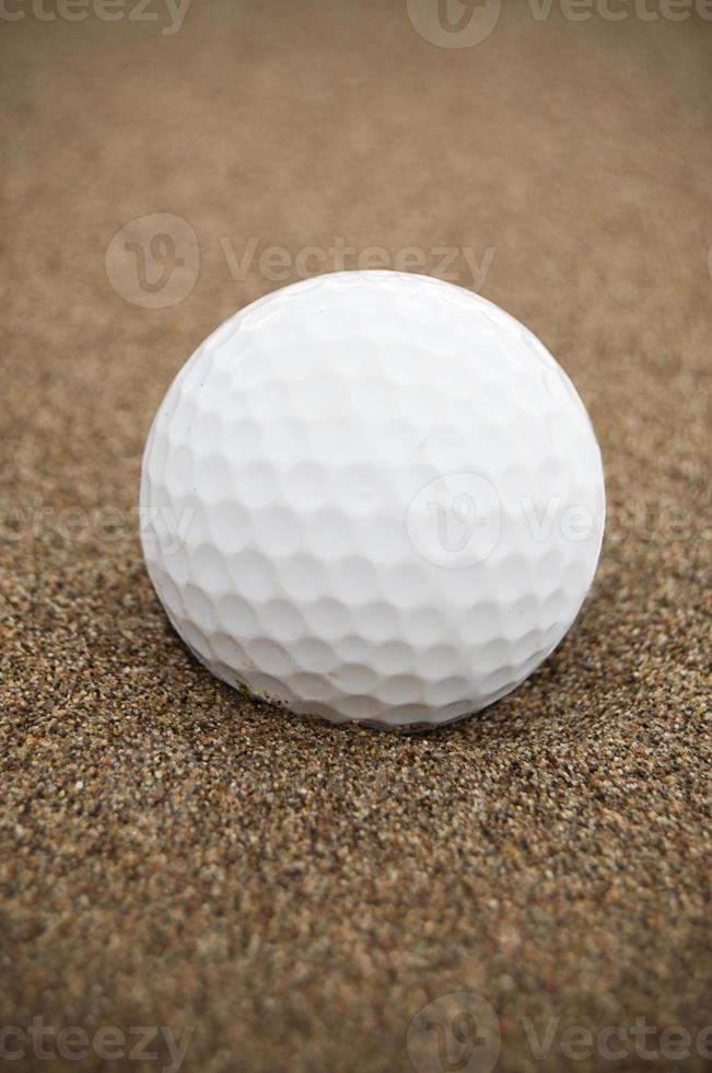 pelota de golf en trampa de arena vertical foto