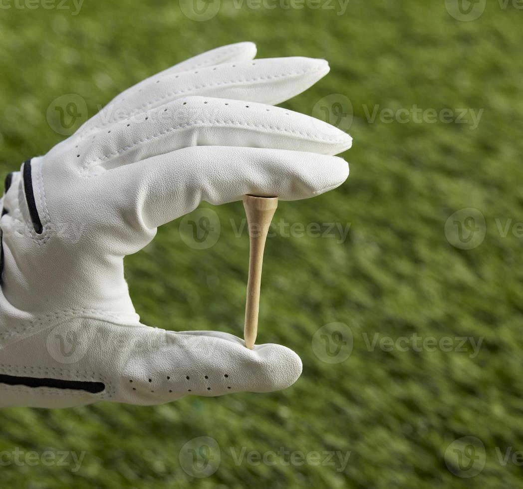 mano humana con tee de golf foto