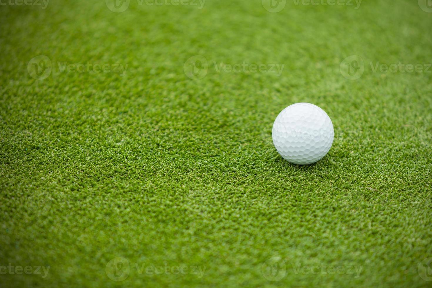 pelota de golf en el verde césped foto