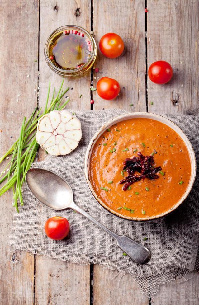 Sopa de tomate con tomates secados al sol. fondo de madera foto