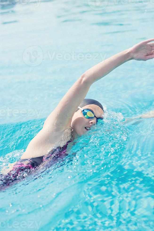 Woman in goggles swimming front crawl style photo