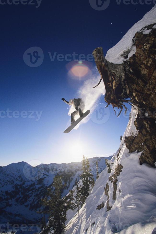 Snowboarder springt vom Bergvorsprung foto