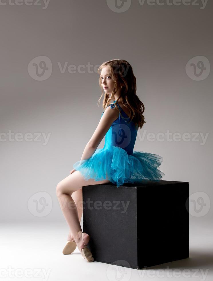 pequeña y linda bailarina posando en cubo en estudio foto