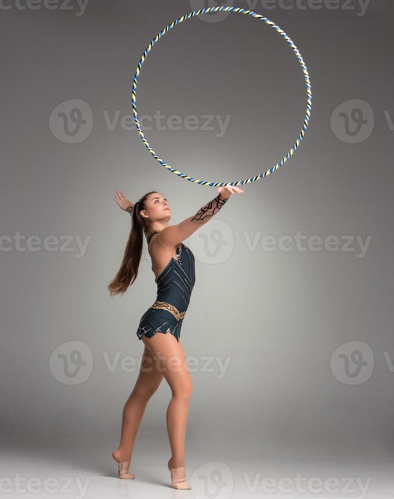 adolescente fazendo exercícios de ginástica com aro de ginástica foto