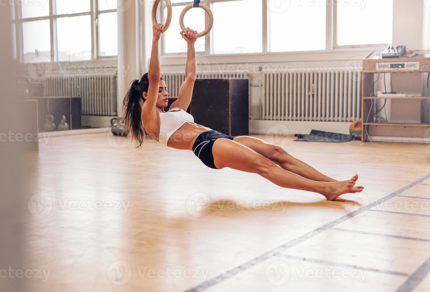 joven fit mujer tirando de anillos de gimnasia foto