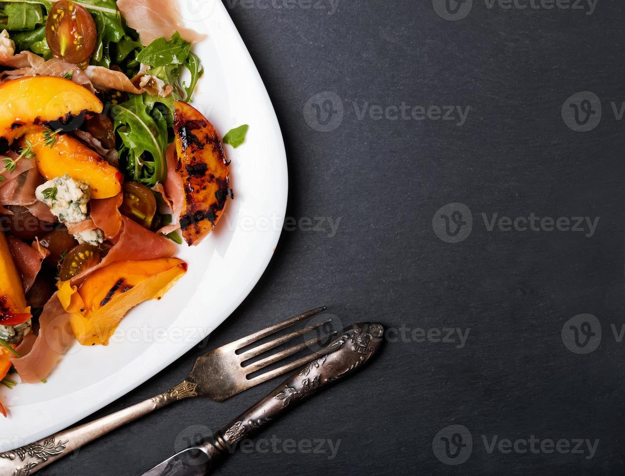 Dark style photo of delicious salad with grilled peaches