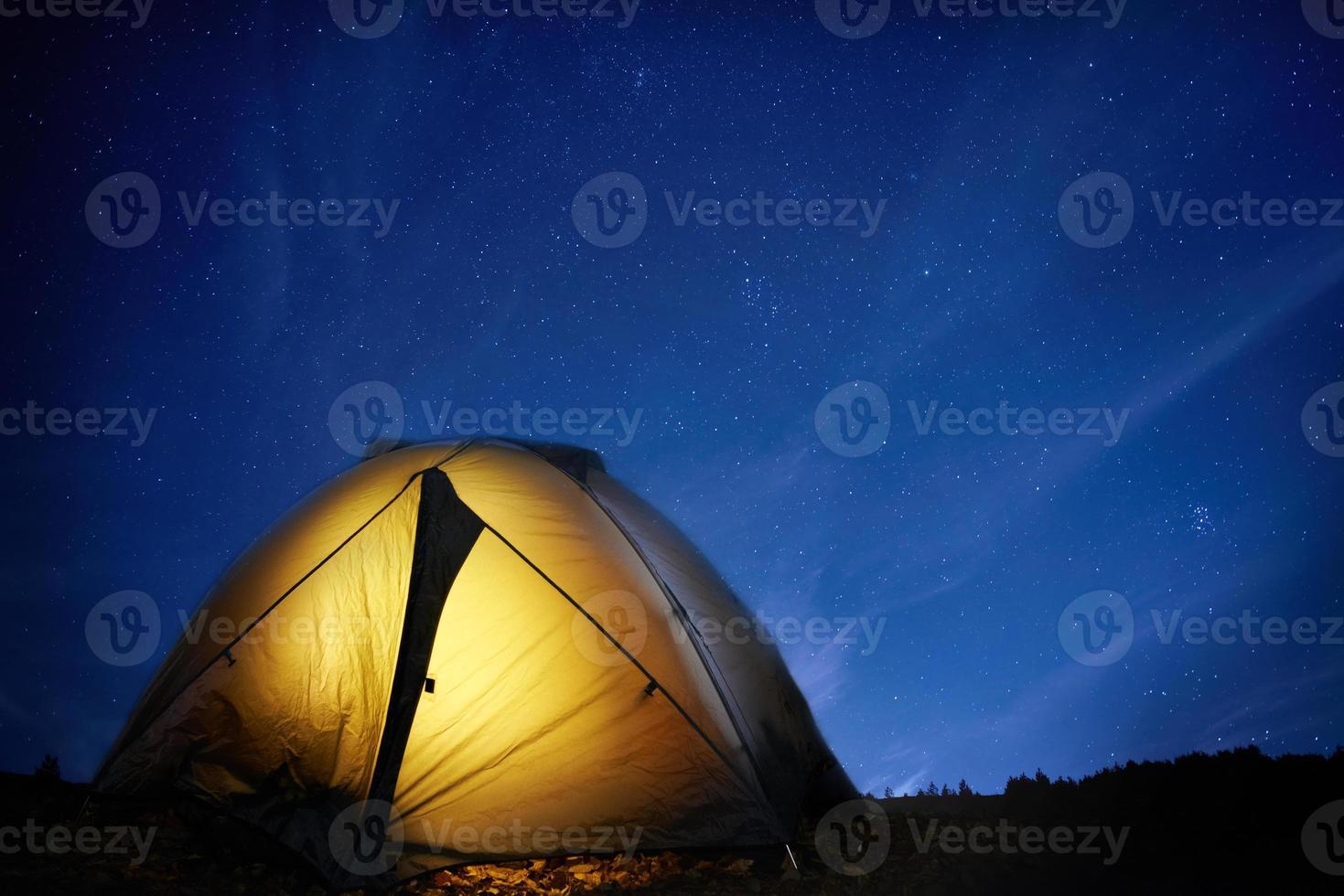 Illuminated yellow camping tent photo