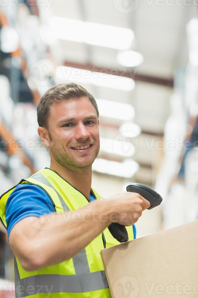 Smiling manual worker scanning package photo