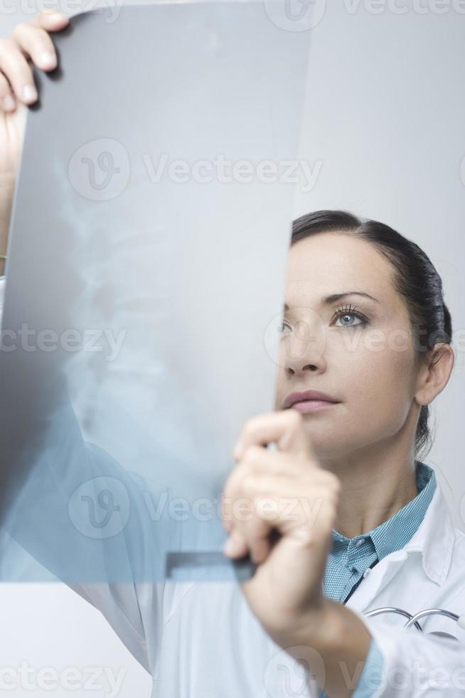 Female radiologist checking x-ray image photo