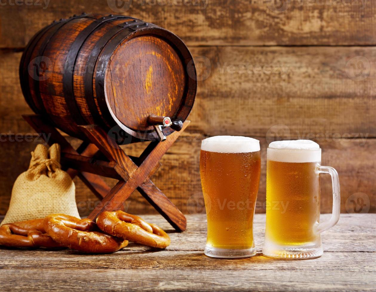 glasses of beer with wooden barrel photo