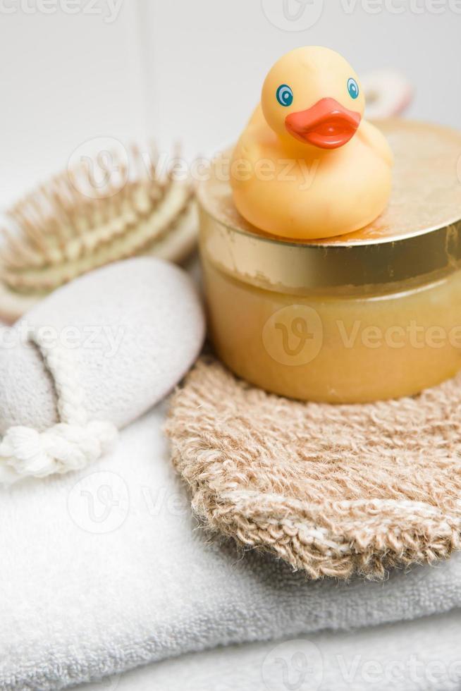 bienestar, pato de goma, piedra pómez, peluquería y guante sobre toalla foto