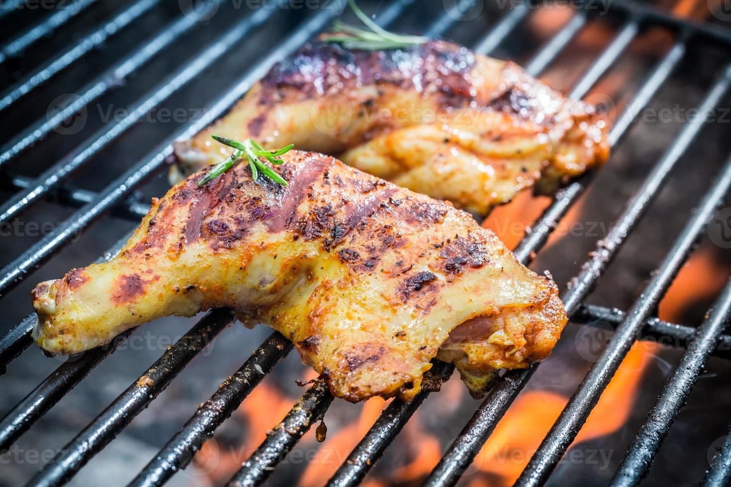 Roasted chicken legs on the grill with fire photo