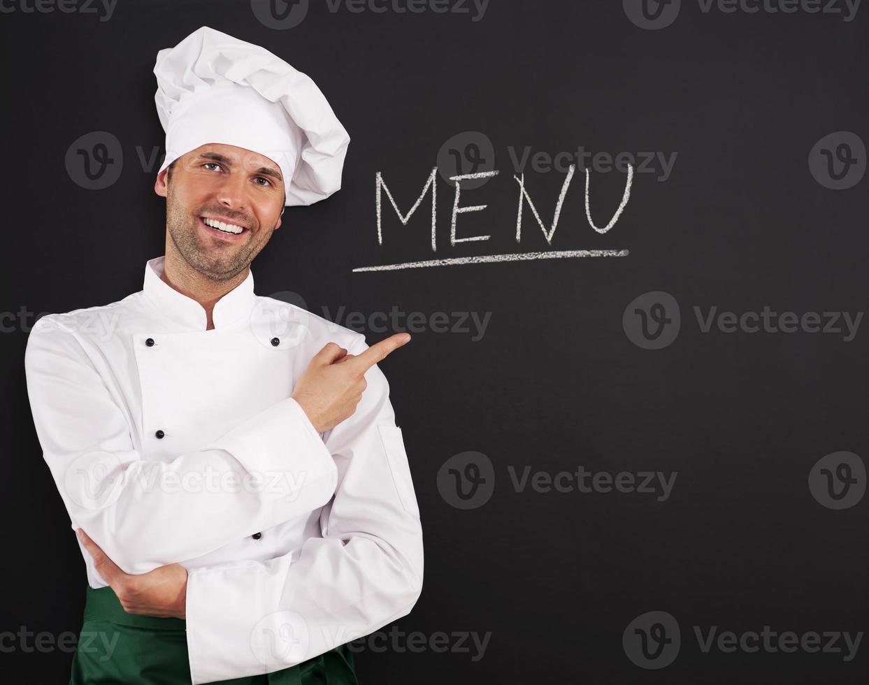 guapo chef mostrando menú foto
