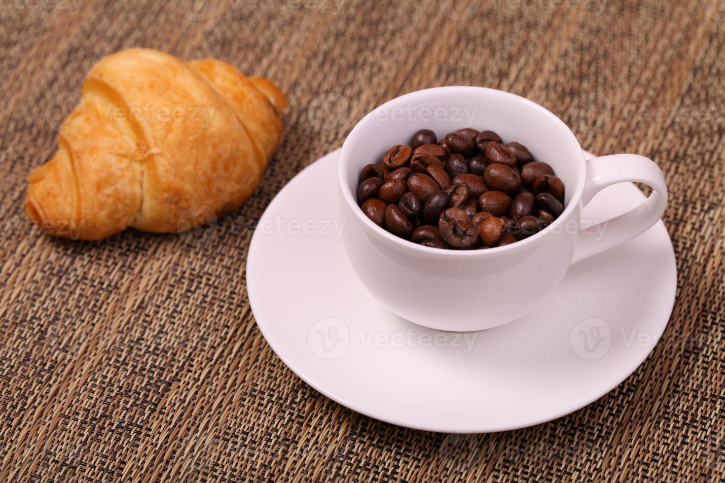 taza de café con un croissant y granos de café recién hechos foto