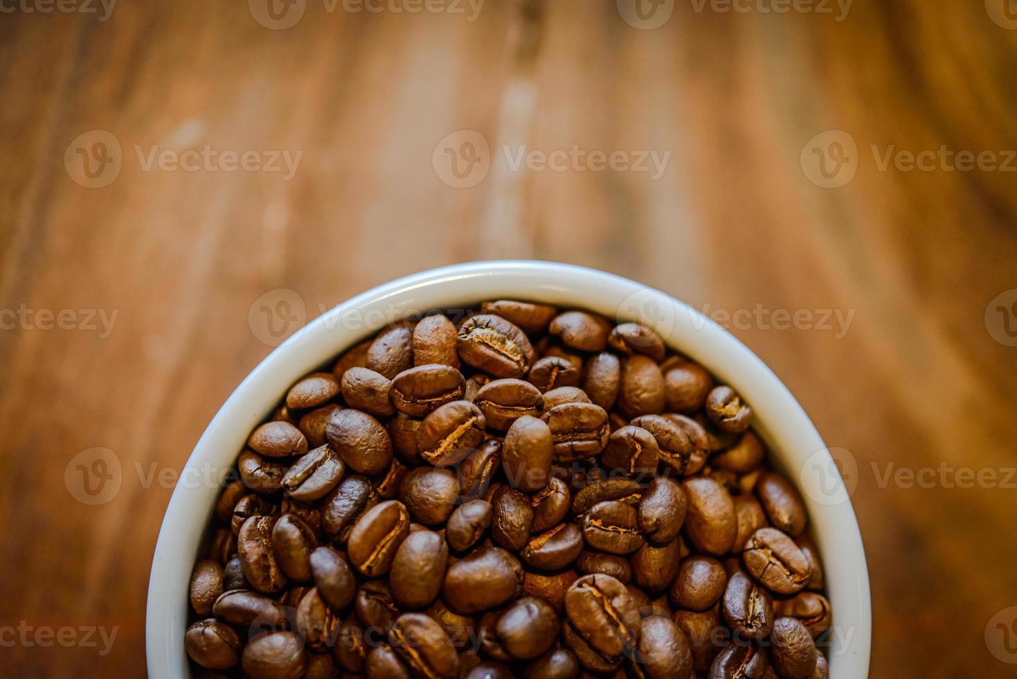 Granos de café en copa sobre fondo de madera grunge foto