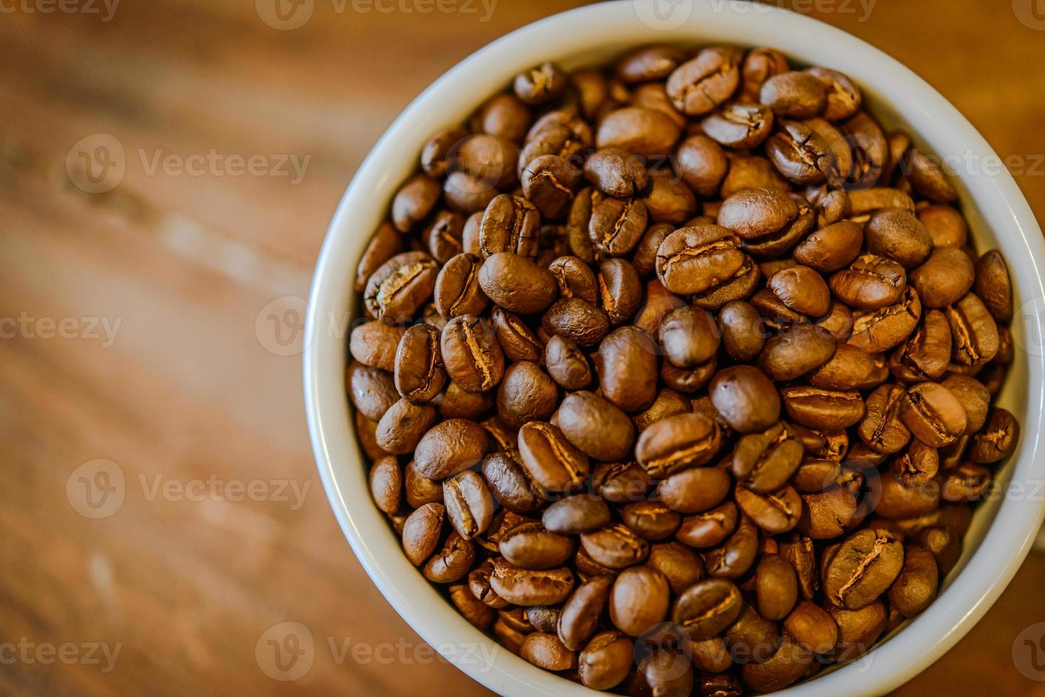 Coffee beans in cup on grunge wooden background photo