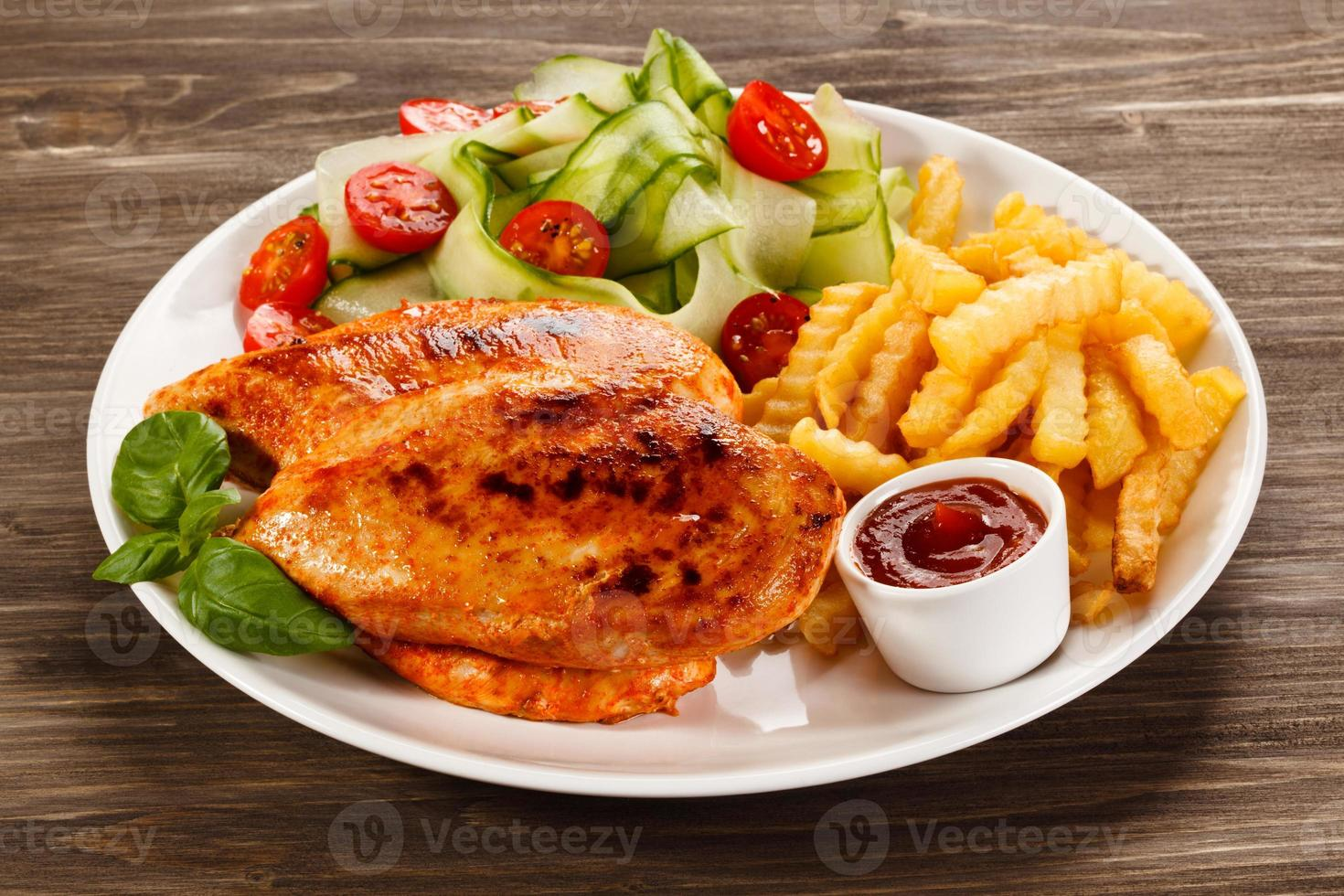 Barbecued chicken fillets, French fries and vegetables on white background photo