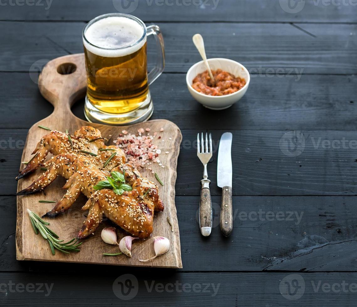 alitas de pollo fritas en una tabla de servir rústica, salsa de tomate picante foto