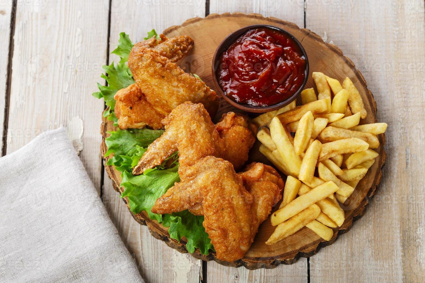 alitas de pollo fritas con salsa y papas fritas foto