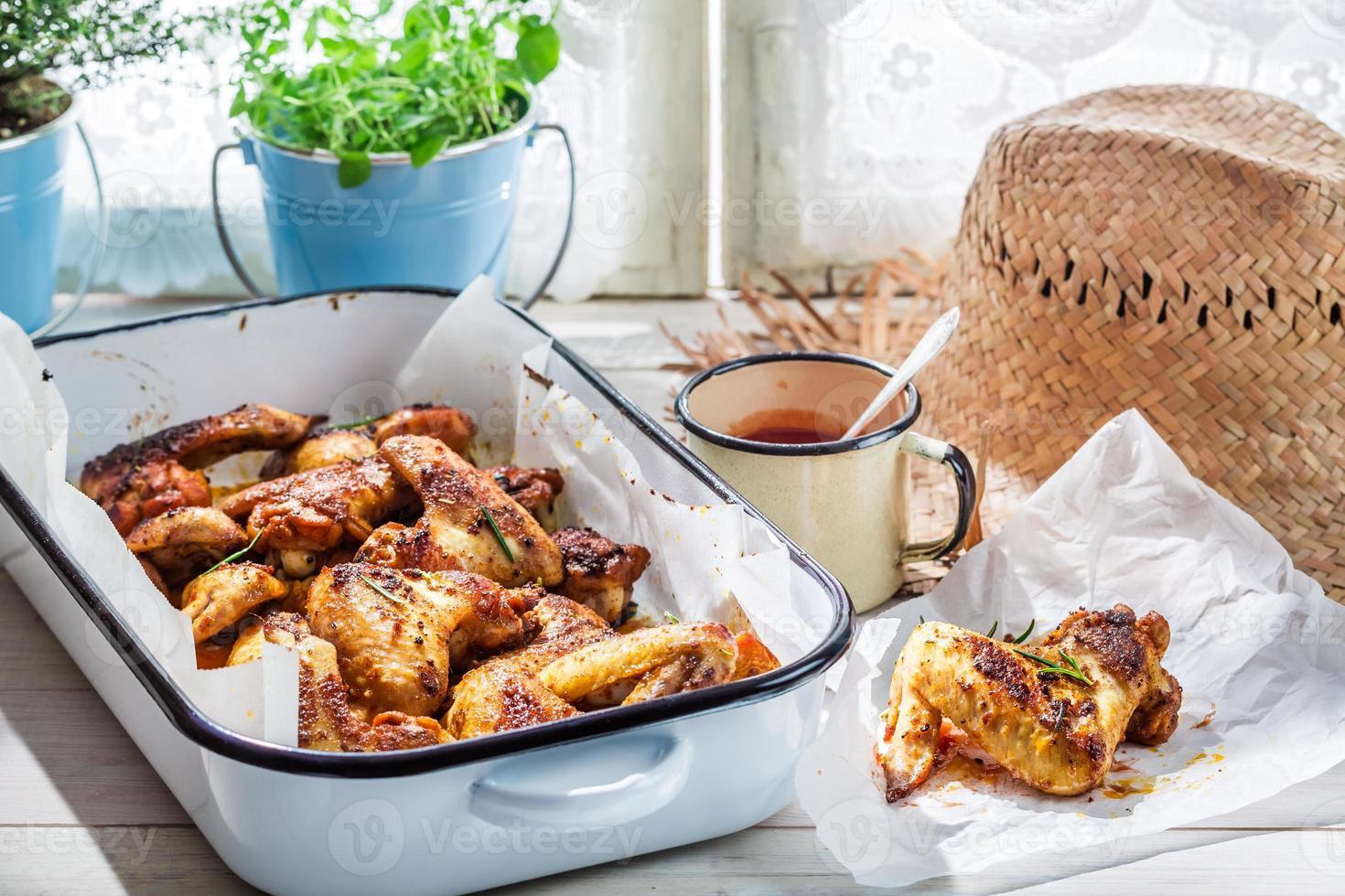 Tasty chicken wings in summer kitchen photo