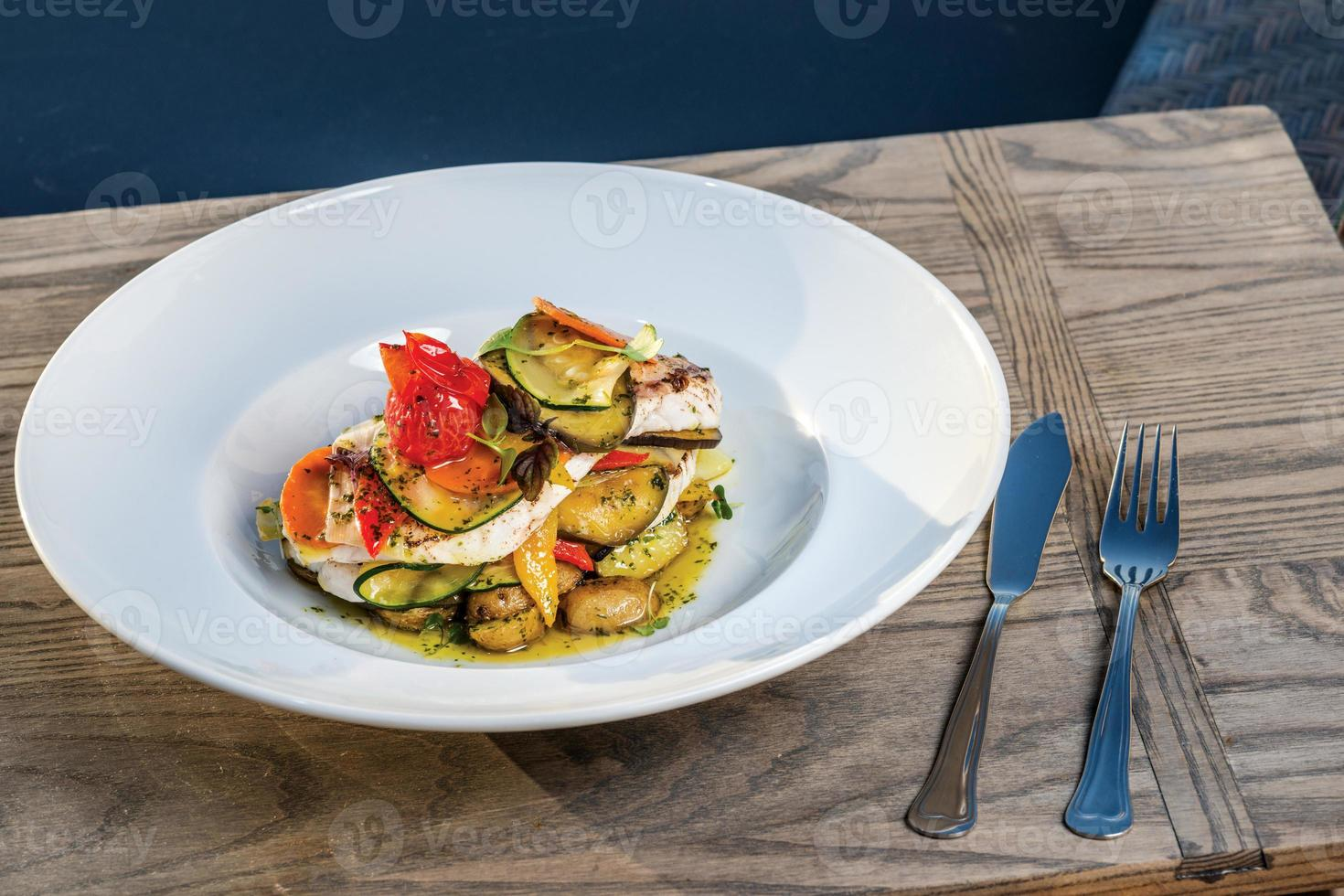 Sea fish dish with mushrooms and grilled vegetables photo