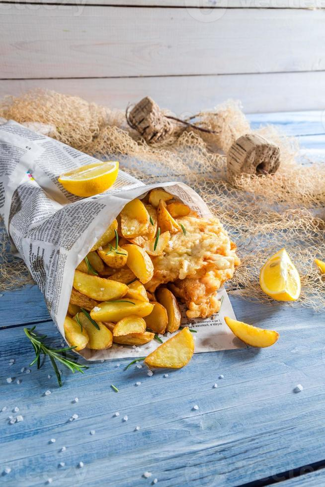 Hot fish cod with chips in newspaper with lemon photo